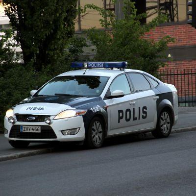 Polisbil på trottoarkant.