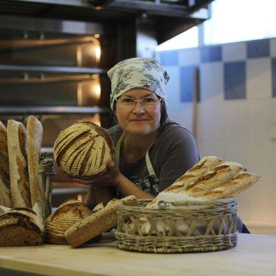 Johanna Hasu från bageriet Leipä ja poika står vid disken med bröd bredvid sig.