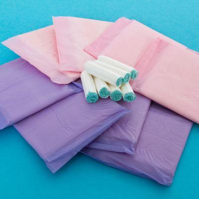 Oanvända dambindor och tamponger i en hög. Turkosblå bakgrund.