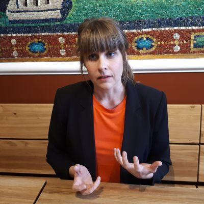 Stina Bäckström sitter vid ett bord