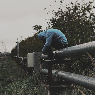 Pojke sitter på staket