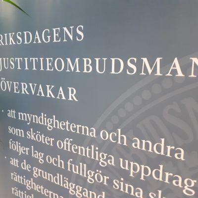 En skylt i riksdagen med texten Riksdagens justitieombudsman övervakar, och exempel på något område