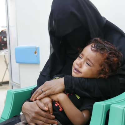 En mor som håller om sin koleradrabbade son.