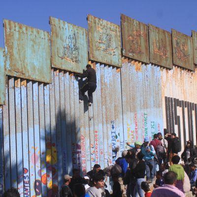 Ett tiotal centralamerikaner som klättrade över stängslet, greps genast av amerikanska gränsvakter