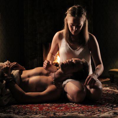 Mies ja nainen lattialla, mies makaa pää naisen sylissä.