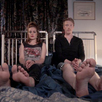 Mies ja nainen istuvat sängyllä.