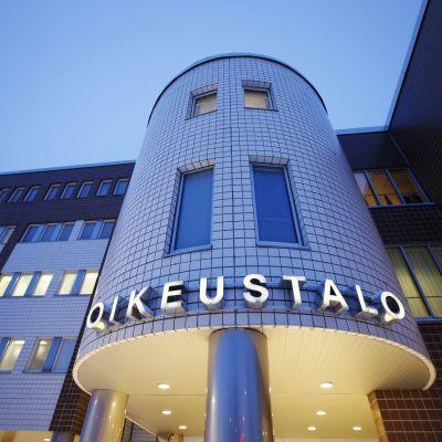 Fasaden av tingshuset i Uleåborg är upplyst nattetid.