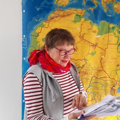 Toimittaja ja ohjaaja Tiina Harpf käsikirjoituspinon kanssa maailmankartan edessä.