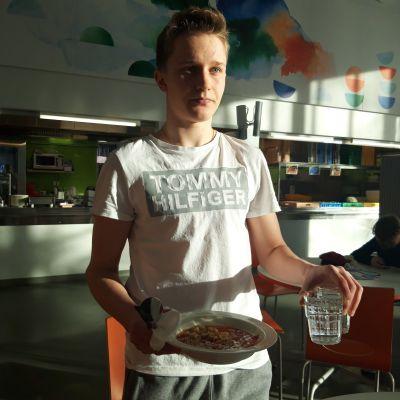 Jasper Nupponen kantaa keittolautasta. Hatsalan koulussa ruokaillaan ilman tarjotinta.
