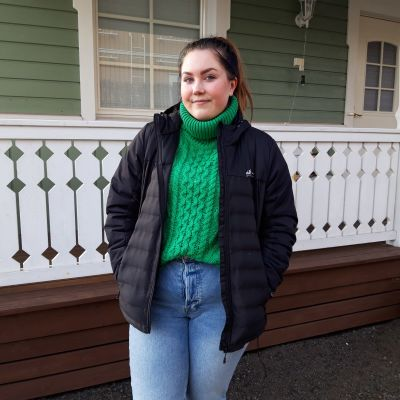Ung kvinna i grön tröja och svart jacka utanför hus.