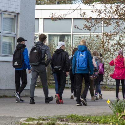 Skolungdomar på väg in på skolgården.