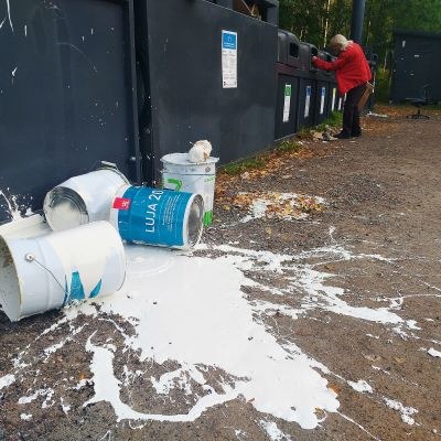 Kaatuneita maalipurkkeja ja maahan roiskunutta maalia kierrätyspisteellä.