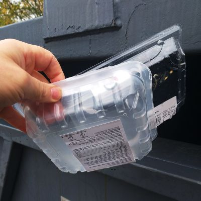 Henkilö laittaa tyhjiä muovipakkauksia muovinkeräykseen.