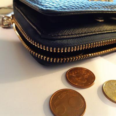 En blå plånbok med några utfällda mynt på ett bord