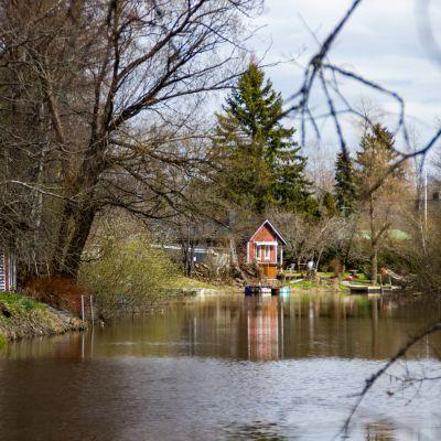 En å och hus vid åstranden.