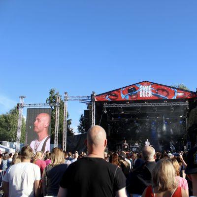 Juha Tapio esiintyy Simerockin lavalla, yleisöä on lavan edessä.