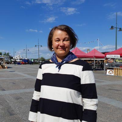 Anu Talka Lappeenrannan satamassa kesällä. Talkalla on päällä mustavalkoinen mekko. Sää on aurinkoinen ja taivas pilvetön.