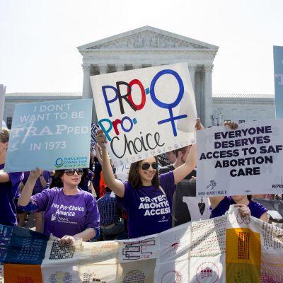 Aborttioikeutta kannattavat mielenosoittajat pitävät käsissään plakaatteja Washingtonin korkeimman oikeuden rakennuksen edustajalla.