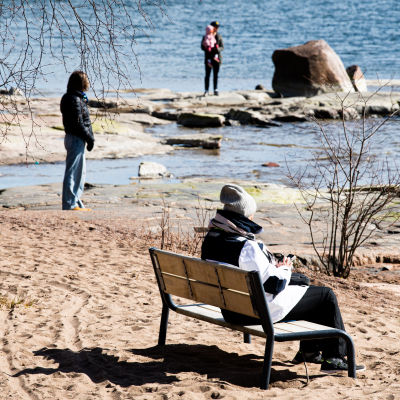 Fyra människor på en solig strand tidigt på våren, människorna är varmt klädda och det finns inga löv på träden ännu.