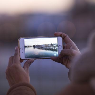 En människa håller i en mobiltelefon och tar en bild med telefonen.