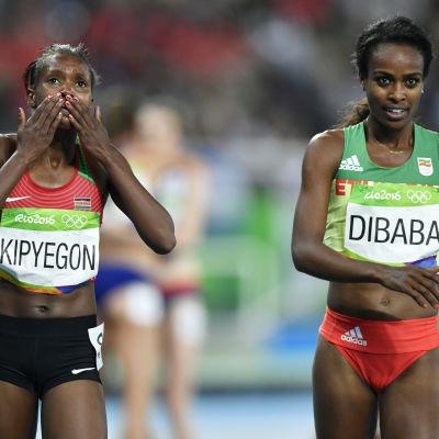 Två kvinnliga afrikanska löpare sida vid sida efter lopp.