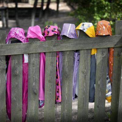 Barns regnrockar hänger på ett staket
