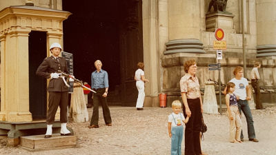En bild från 70-talet där Petri håller i sin mammas hand utanför ett slott. I bakgrunden en vakt.