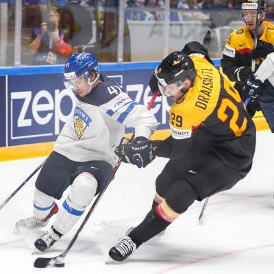 Ishockeyspelare i kamp om puck.
