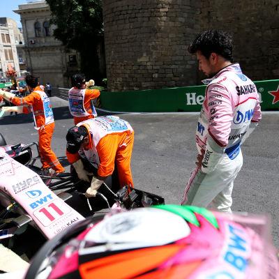 Sergio Perez tittar på då bilen förs iväg