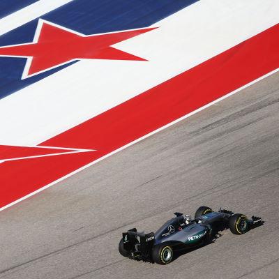 Lewis Hamilton kör bredvid en stor logotyp på vänster sida.