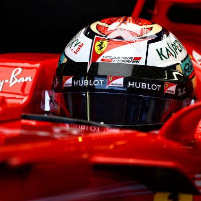 Räikkönen sitter med hjälmen på i bilen.