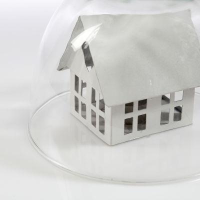 Vitt miniatyrhus under en glaskupa.