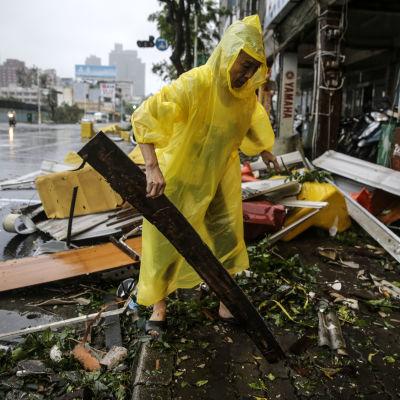 En man reder upp bråte efter orkanen