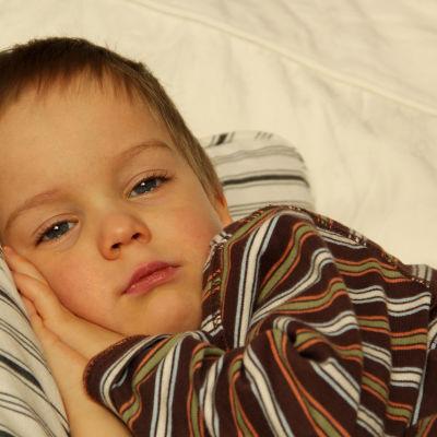 Förkyld 3-årigpojke vilar på soffa.