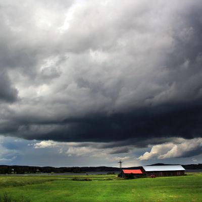 Regntunga moln över jordbruk.