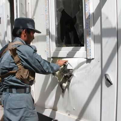 En afghansk polis undersöker skadorna efter en talibanattack.
