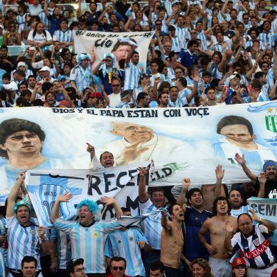 Banner med Maradona, Påven och Messi, under VM-finalen i fotboll.