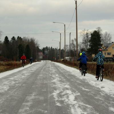 Barn cyklar längs Veikarsvägen i Korsholm