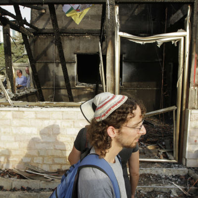 Israeliska fredsaktivister utanför huset till familjen som utsattes för en brandbombsattack  i juli 2015.
