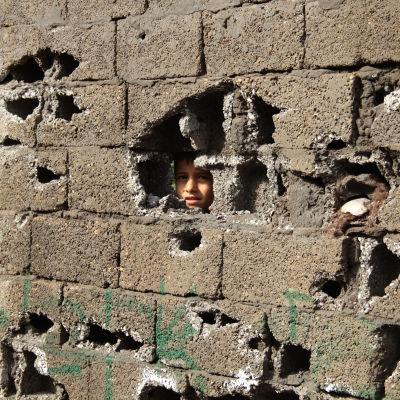 Kurdiska pojke tittar ut genom sönderskjuten mur i Cizre