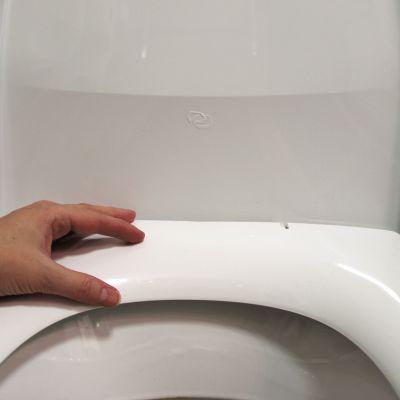 Hand som vilar mot toalettkrans.