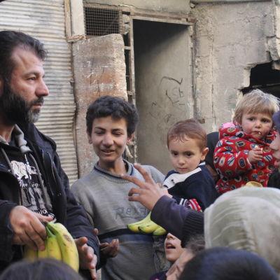 Rami Adham delar ut bananer åt barnen i Aleppo.