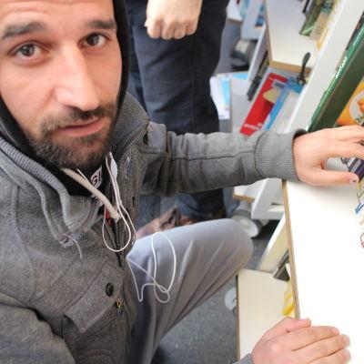 En asylsökande bläddrar i bokbussens utbud.