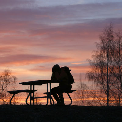 Person vid bord i solnedgång.