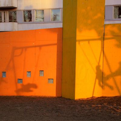 En orange husvägg med skuggorna från barn som gungar och vuxna som ger fart i en lekpark.