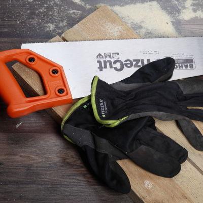 Bild på handskar och såg som lagts åt sidan.
