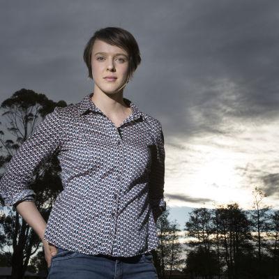 Sarah Thomson står framför en skogsbakgrund i solnedgången.