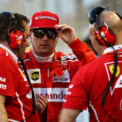 Kimi Räikkönen och ingenjörer samtalar.
