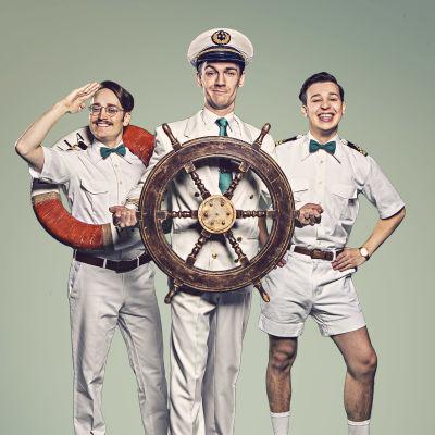 Tre unga män i sjömanskostymer poserar för kameran. Mannen i mitten har ett roder i handen. Mannen till vänster har en livboj runt halsen