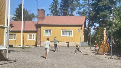Elever spelar fotboll på en gårdsplan.